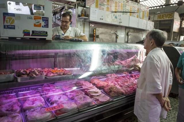 CAR10 - CARACAS (VENEZUELA), 02/11/2017 - Un hombre pregunta por los precios de la carne en un mercado popular hoy, 2 de noviembre del 2017, en Maracaibo (Venezuela). Venezuela registró este mes de octubre una inflación del 50,6 %, respecto del mes anterior, entrando técnicamente en hiperinflación al rebasar por primera vez en su historia el umbral del 50 % que define este último concepto. EFE/MIGUEL GUTIÉRREZ