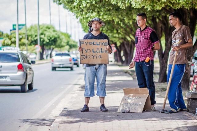 Fotografìa del 01 de noviembre de 2017, de migrantes venezolanos que solicitan trabajo con un cartel en una calle de Boa Vista, en el estado de Roraima (Brasil). Miles de venezolanos dejan su país en busca de una nueva vida en Brasil, en áreas como el estado amazónico de Roraima, una deprimida región del norte que ha pedido ayuda al Gobierno de Michel Temer para afrontar la avalancha de solicitudes de refugio recibidas en el último año. EFE / GILDO JUNIOR