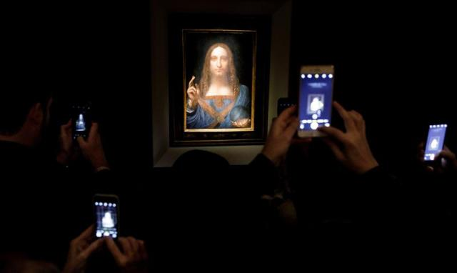 Varias personas fotografían la obra 'Salvator Mundi' del artista Leonardo da Vinci (1500), durante una vista previa pública antes de que la casa Christie's lo subaste por un precio estimado de 100 millones de dólares, en Nueva York (Estados Unidos) hoy, 15 de noviembre de 2017. 'Salvator Mundi' es la única obra del polímata florentino que queda en manos privadas. EFE/ Justin Lane