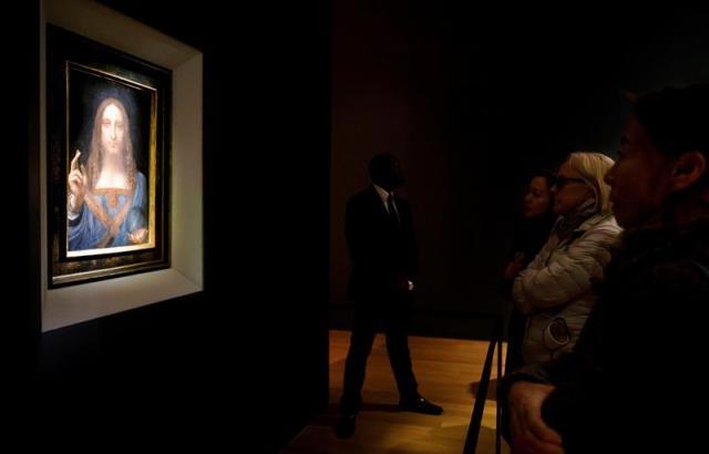 Varias personas observan la obra 'Salvator Mundi' del artista Leonardo da Vinci (1500), durante una vista previa pública antes de que la casa Christie's lo subaste por un precio estimado de 100 millones de dólares, en Nueva York (Estados Unidos) hoy, 15 de noviembre de 2017. 'Salvator Mundi' es la única obra del polímata florentino que queda en manos privadas. EFE/ Justin Lane
