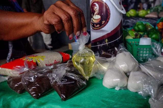 ACOMPAÑA CRÓNICA: VENEZUELA CRISIS - CAR005. CARACAS (VENEZUELA), 19/11/2017.- Fotografía del 17 de noviembre de 2017, que muestra a una vendedora informal mientras sostiene una bolsa de aceite vegetal, que ofrece a la venta junto a azúcar y café en un puesto en una calle de Caracas (Venezuela). Venezuela es el país del mundo con mayores reservas de petróleo, pero el empobrecimiento de sus habitantes les ha abocado a comprar cucharadas de comida para intentar burlar una escasez de alimentos que se ha agravado en los últimas semanas, cuando la economía entró en una espiral hiperinflacionaria. Productos de consumo diario como el café, la harina, la leche y el azúcar son ofrecidos ahora en bolsitas que pesan entre 50 y 150 gramos, cuyos precios suben cada día en los puestos ambulantes de los barrios populares al margen de las regulaciones impuestas por el Gobierno de Nicolás Maduro. EFE/Cristian Hernández