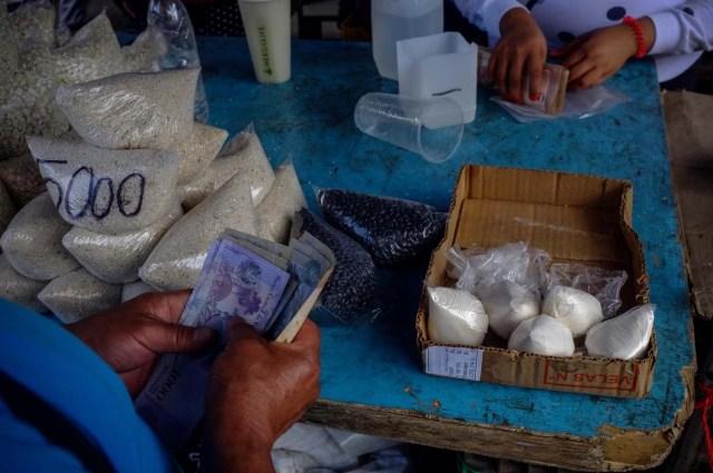 ACOMPAÑA CRÓNICA: VENEZUELA CRISIS - CAR008. CARACAS (VENEZUELA), 19/11/2017.- Fotografía del 17 de noviembre de 2017, que muestra bolsas de leche a la venta en un puesto informal en una calle de Caracas (Venezuela). Venezuela es el país del mundo con mayores reservas de petróleo, pero el empobrecimiento de sus habitantes les ha abocado a comprar cucharadas de comida para intentar burlar una escasez de alimentos que se ha agravado en los últimas semanas, cuando la economía entró en una espiral hiperinflacionaria. Productos de consumo diario como el café, la harina, la leche y el azúcar son ofrecidos ahora en bolsitas que pesan entre 50 y 150 gramos, cuyos precios suben cada día en los puestos ambulantes de los barrios populares al margen de las regulaciones impuestas por el Gobierno de Nicolás Maduro. EFE/Cristian Hernández