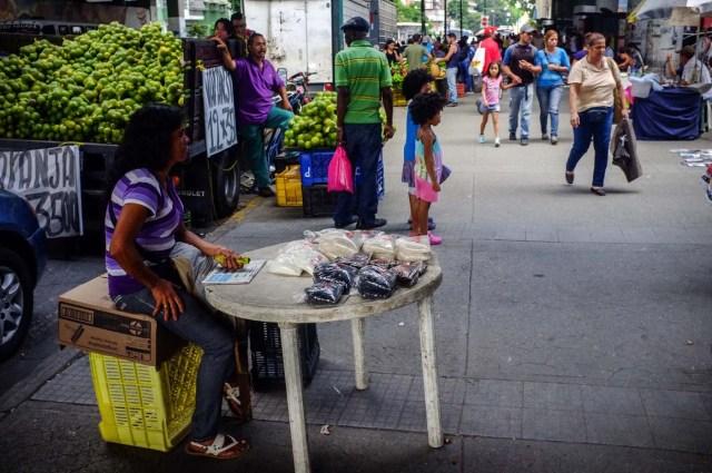 ACOMPAÑA CRÓNICA: VENEZUELA CRISIS - CAR010. CARACAS (VENEZUELA), 19/11/2017.- Fotografía del 17 de noviembre de 2017, que muestra una vendedora informal mientras espera por clientes en un puesto en una calle de Caracas (Venezuela). Venezuela es el país del mundo con mayores reservas de petróleo, pero el empobrecimiento de sus habitantes les ha abocado a comprar cucharadas de comida para intentar burlar una escasez de alimentos que se ha agravado en los últimas semanas, cuando la economía entró en una espiral hiperinflacionaria. Productos de consumo diario como el café, la harina, la leche y el azúcar son ofrecidos ahora en bolsitas que pesan entre 50 y 150 gramos, cuyos precios suben cada día en los puestos ambulantes de los barrios populares al margen de las regulaciones impuestas por el Gobierno de Nicolás Maduro. EFE/Cristian Hernández