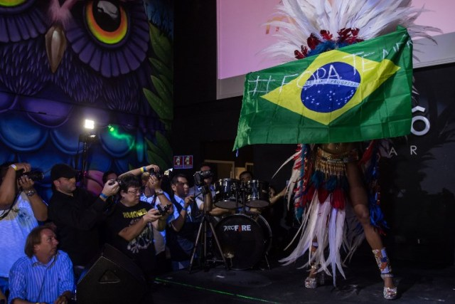 """Rosie Oliveira from Amazonas holds a Brazilian national flag with an inscription reading """"Temer out"""" (a reference to Brazilian President Michel Temer) during the Miss Bumbum Brazil 2017 pageant in Sao Paulo on November 07, 2017. Fifteen candidates competed in the annual pageant to select the Brazil's sexiest female rear end. / AFP PHOTO / NELSON ALMEIDA"""