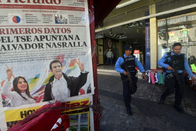 The front page of a local newspaper shows Honduran opposition candidate Salvador Nasralla and his wife Iroshka Elvir, at a stand in Tegucigalpa on November 27, 2017, a day after the general election. Initial election results released early Monday in Honduras showed opposition candidate Salvador Nasralla leading President Juan Orlando Hernandez, after a tense evening that saw both men declare themselves the winner before official numbers were announced. / AFP PHOTO / Rodrigo ARANGUA
