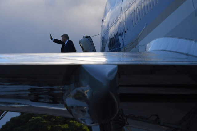 US President Trump waves as he embarks on Air Force One leaving Hawaii for Japan on November 04, 2017. After stopping in Hawaii to pay his respects at a Pearl Harbor memorial, US President Donald Trump reboarded Air Force One on Saturday for a marathon Asia tour as North Korea's nuclear threat looms large. / AFP PHOTO / JIM WATSON