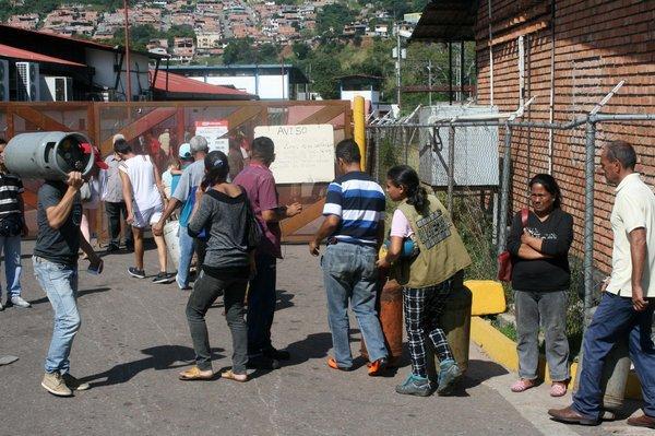 Mujeres y hombres soportan tediosas horas de espera para lograr adquirir una bombona de gas. (foto Tulia Buriticá)