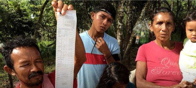 Luciano Mendoza, a la izquierda, el supervisor electoral del Partido Socialista en el pueblo de El Casabe, mostró recientemente un recibo de máquina de votación que contó menos votos de los que las autoridades electorales informaron más tarde. Algunos de los miembros de su familia están detrás de él. ANATOLY KURMANAEV / THE WALL STREET JOURNAL