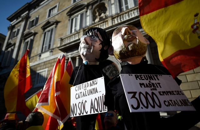 Demonstrators carry two puppets representing deposed Catalan president and vice-president, Carles Puigdemont (L) and imprisoned Oriol Junqueras during an against-independence and in favour of Spanish Constitution demonstration called by 'Movimiento Civico D'Espanya i Catalans' (Civic movement of Spain and the Catalans) in Barcelona on december 6, 2017. / AFP PHOTO / Josep LAGO