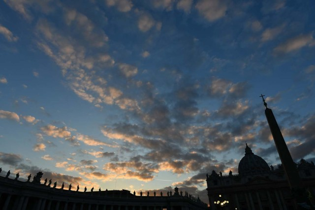 St Peter's basilica and the statues on the top of the colonnade are silhouetted at sunset on December 7, 2017 in Vatican. / AFP PHOTO / Alberto PIZZOLI