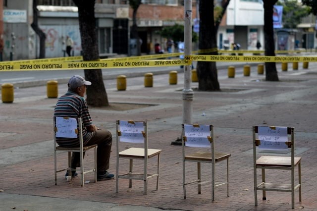 A man waits outside a polling station to cast his vote during municipal elections in Caracas on December 10, 2017. / AFP PHOTO / FEDERICO PARRA