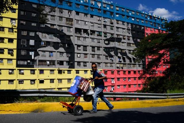 """Un hombre empuja una carreta en la calle frente a un edificio que representa los ojos del difunto presidente venezolano Hugo Chávez en el vecindario"""" 23 de Enero """"en Caracas el 15 de diciembre de 2017."""