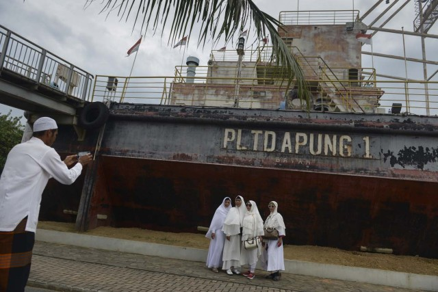 """Acehnese pose for a photo next to a ship-turned-into a memorial which was pushed some 2.5 kilometres (1.55 miles) inland by the 2004 tsunami in Banda Aceh on December 26, 2017, as visitors remember one of the worst natural disasters in human history. Some 170,000 lives were lost in the country when a 9.1-magnitude """"megathrust"""" quake struck Aceh, a predominantly Muslim province in the northern tip of Sumatra island, bringing about massive waves that also hit coastal areas as far away as Somalia and killing 50,000 others in various countries. / AFP PHOTO / CHAIDEER MAHYUDDIN"""