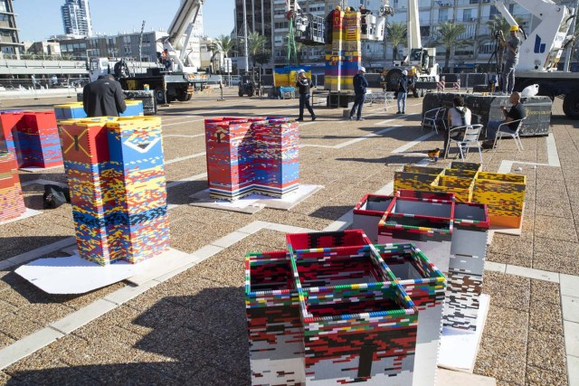 Workers and volunteers help assemble bricks during the construction of a LEGO tower in Tel Aviv's Rabin Square on December 26, 2017, as the city attempts to break Guinness world record of the highest such structure. / AFP PHOTO / JACK GUEZ