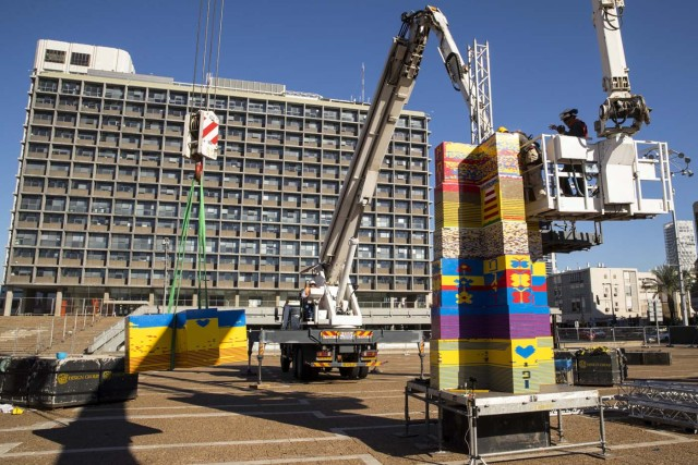 Workers and volunteers help assemble bricks during the construction of a LEGO tower in Tel Aviv's Rabin Square on December 26, 2017, as the city attempts to break Guinness world record of the highest such structure and for it to exceed the height of the municipality building, seen in the background. / AFP PHOTO / JACK GUEZ