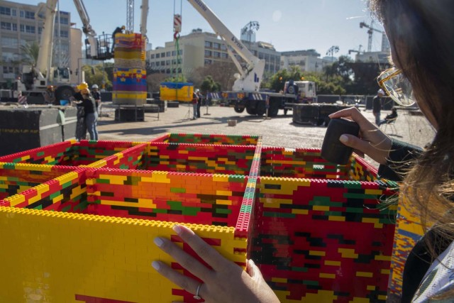 A woman assembles bricks as she works on a component of a LEGO tower under construction in Tel Aviv's Rabin Square on December 26, 2017, as the city attempts to break Guinness world record of the highest such structure. / AFP PHOTO / JACK GUEZ