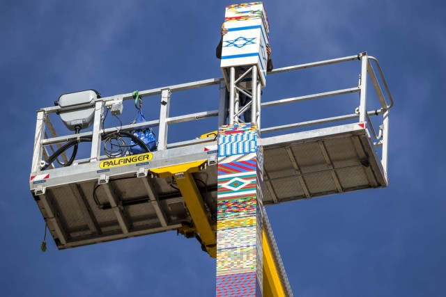 A man helps fix the top of a LEGO tower under construction in Tel Aviv on December 27, 2017, as the city attempts to break Guinness world record of the highest such structure. / AFP PHOTO / JACK GUEZ
