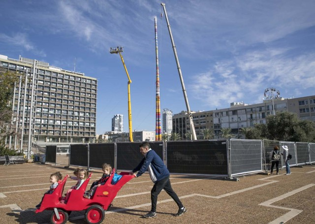 A man pushes a child stroller as he passes by a LEGO tower under construction in Tel Aviv's Rabin Square on December 27, 2017, as the city attempts to break Guinness world record of the highest such structure. / AFP PHOTO / JACK GUEZ