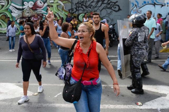 People shout slogans during a protest against the shortage of food, amid Fuerzas Armadas avenue in Caracas on December 28, 2017. As Venezuelans protest in Caracas demanding the government's prommised pork -the main dish of the Christmas and New Year's dinner-, President Nicolas Maduro attributes the shortage to international sabotage. / AFP PHOTO / FEDERICO PARRA