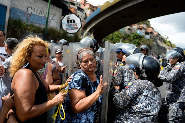 People confront riot police during a protest against the shortage of food, amid Fuerzas Armadas avenue in Caracas on December 28, 2017. As Venezuelans protest in Caracas demanding the government's prommised pork -the main dish of the Christmas and New Year's dinner-, President Nicolas Maduro attributes the shortage to international sabotage. / AFP PHOTO / FEDERICO PARRA