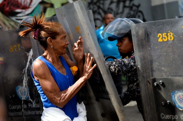A woman confronts riot police during a protest against the shortage of food, amid Fuerzas Armadas avenue in Caracas on December 28, 2017. As Venezuelans protest in Caracas demanding the government's prommised pork -the main dish of the Christmas and New Year's dinner-, President Nicolas Maduro attributes the shortage to international sabotage. / AFP PHOTO / FEDERICO PARRA