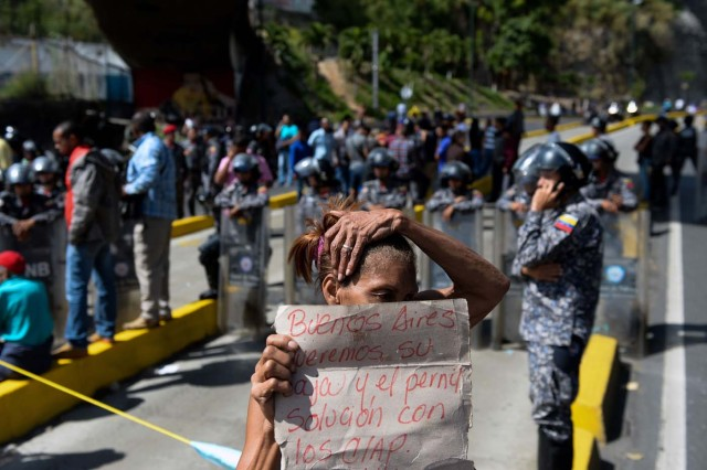 Venezuelans take part in a protest against the shortage of food in Caracas on December 28, 2017. As Venezuelans protest in Caracas demanding the government's prommised pork -the main dish of the Christmas and New Year's dinner-, President Nicolas Maduro attributes the shortage to international sabotage. / AFP PHOTO / FEDERICO PARRA