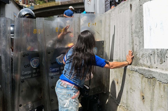 A woman confronts riot police during a protest against the shortage of food in Caracas on December 28, 2017. As Venezuelans protest in Caracas demanding the government's prommised pork -the main dish of the Christmas and New Year's dinner-, President Nicolas Maduro attributes the shortage to international sabotage. / AFP PHOTO / FEDERICO PARRA
