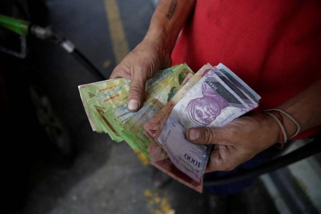 Un trabajador cuenta bolívares venezolanos en una gasolinera de la petrolera estatal venezolana PDVSA en Caracas, Venezuela, el 1 de diciembre de 2017. REUTERS / Marco Bello