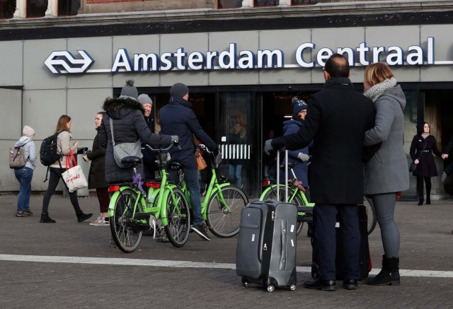 People walk near rental bicycles outside central station in Amsterdam, Netherlands, December 1, 2017. REUTERS/Yves Herman