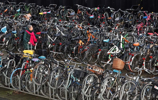A woman pulls her luggage while walking among hundreds of bicycles outside central train station in Amsterdam, Netherlands, December 1, 2017. REUTERS/Yves Herman