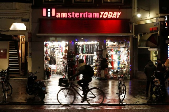 A cyclist rides past a touristic shop in Amsterdam, Netherlands, December 1, 2017. REUTERS/Yves Herman