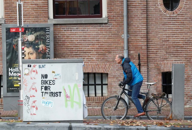 """A cyclist rides past a graffiti reading """"no bikes for tourist"""" in central Amsterdam, Netherlands, December 1, 2017. REUTERS/Yves Herman"""