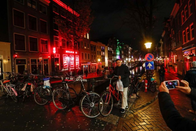 A tourist poses for a photo near a canal in the red district of Amsterdam, Netherlands, November 30, 2017. Picture taken November 30, 2017. REUTERS/Yves Herman