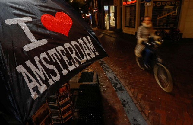 A cyclist rides past a touristic shop in the red district of Amsterdam, Netherlands, November 30, 2017. Picture taken November 30, 2017. REUTERS/Yves Herman