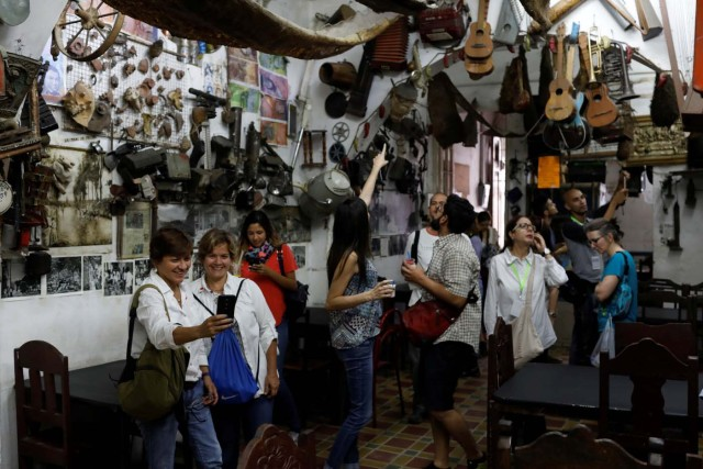 Attendees of a walking tour of 'Caracas in 365' look around inside 'Bar El Torero' (The Bullfighter) at Catia neighborhood in Caracas, Venezuela November 18, 2017. Picture taken November 18, 2017. REUTERS/Marco Bello