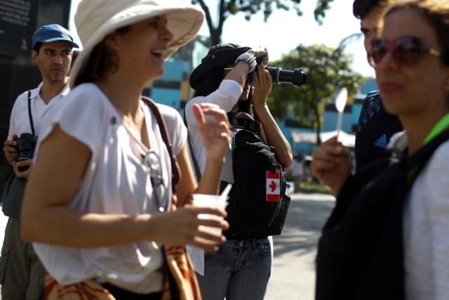 A woman takes photos during a walking tour of 'Caracas in 365' at Catia neighborhood in Caracas, Venezuela November 18, 2017. Picture taken November 18, 2017. REUTERS/Marco Bello