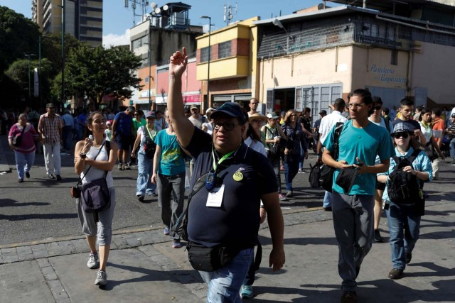 A coordinator of 'Caracas in 365' gedstures to attendees during a walking tour at Catia neighborhood in Caracas, Venezuela November 18, 2017. Picture taken November 18, 2017. REUTERS/Marco Bello