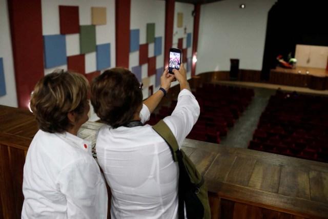 Women take selfies inside the Catia Theater during a walking tour of 'Caracas in 365' at Catia neighborhood in Caracas, Venezuela November 18, 2017. Picture taken November 18, 2017. REUTERS/Marco Bello