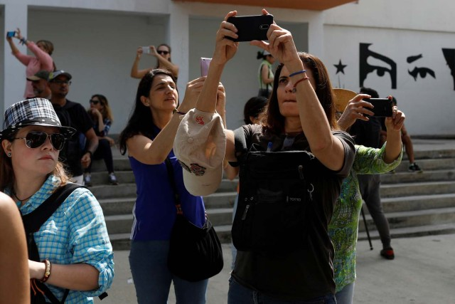 Attendees of a walking tour of 'Caracas in 365' use their phones to take photos in a street at Catia neighborhood in Caracas, Venezuela November 18, 2017. Picture taken November 18, 2017. REUTERS/Marco Bello