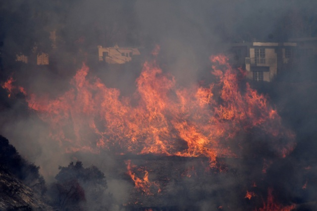 Flames from the Skirball Fire spread on a hillside in a wealthy neighborhood on the west side of Los Angeles, California, U.S., December 6, 2017. REUTERS/Gene Blevins