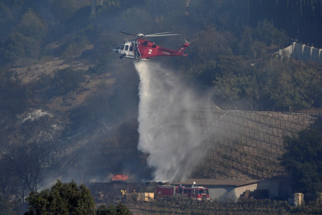 A fire department helicopter makes a water drop building on the vineyard estate of media mogul Rupert Murdoch catches fire during the Skirball fire in Bel Air, a wealthy neighborhood on the west side of Los Angeles, California, U.S., December 6, 2017.      REUTERS/Gene Blevins