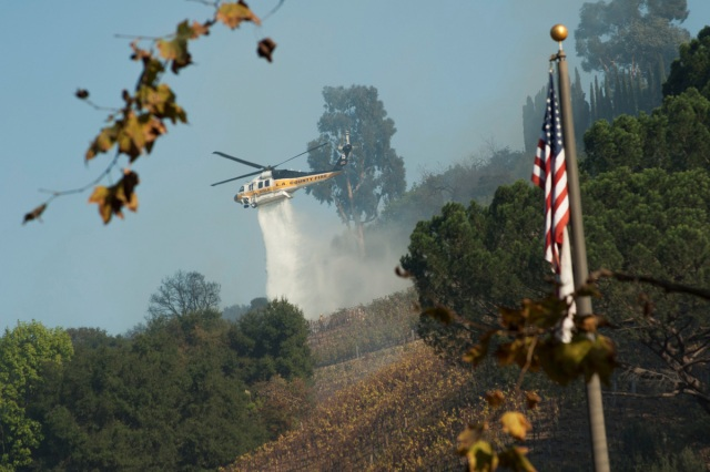 A helicopter drops water on a vineyard owned by Rupert Murdoch damaged by the Skirball fire near the Bel Air neighborhood on the west side of Los Angeles, California, U.S., December 6, 2017.      REUTERS/Andrew Cullen