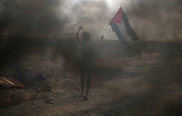 Un manifestante sostiene una bandera palestina durante enfrentamientos con tropas israelíes en una protesta contra la decisión del presidente estadounidense Donald Trump de reconocer a Jerusalén como la capital de Israel, cerca de la frontera con Israel en el sur de la Franja de Gaza el 7 de diciembre de 2017. REUTERS / Ibraheem Abu Mustafa