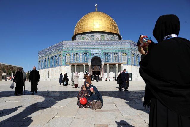 """Turkish tourists pose for a photograph ahead of Friday prayers on the compound known to Muslims as Noble Sanctuary and to Jews as Temple Mount in Jerusalem's Old City, as Palestinians call for a """"day of rage"""" in response to U.S. President Donald Trump's recognition of Jerusalem as Israel's capital December 8, 2017. REUTERS/Ammar Awad"""