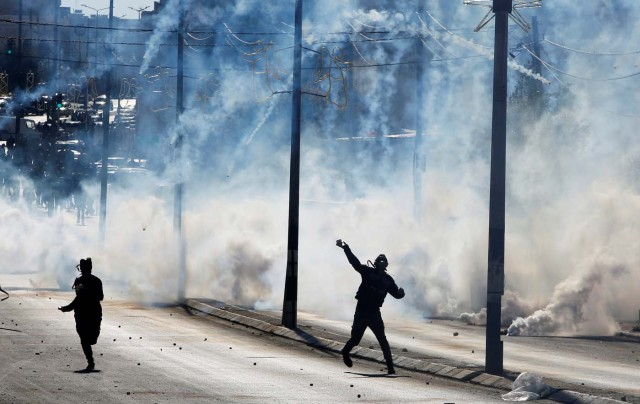 "A Palestinian protester hurls stones as tear gas is fired by Israeli troops during clashes as Palestinians call for a ""day of rage"" in response to U.S. President Donald Trump's recognition of Jerusalem as Israel's capital, in the West Bank city of Bethlehem December 8, 2017. REUTERS/Mussa Qawasma"