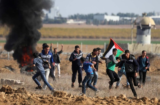 "Palestinian protesters run during clashes as Palestinians call for a ""day of rage"" in response to U.S. President Donald Trump's recognition of Jerusalem as Israel's capital, near the border with Israel in the southern Gaza Strip December 8, 2017. REUTERS/Ibraheem Abu Mustafa"