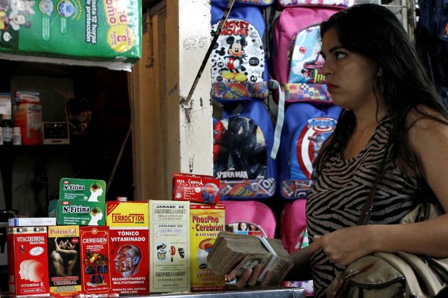 A woman holds a stack of bolivar notes in a stall selling medicines at a market in Rubio, Venezuela December 5, 2017. Picture taken December 5, 2017. REUTERS/Carlos Eduardo Ramirez