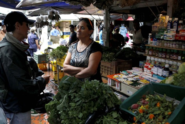 A vendor talks with a customer in her fruit and vegetables stall selling medicines at a market in Rubio, Venezuela December 5, 2017. Picture taken December 5, 2017. REUTERS/Carlos Eduardo Ramirez