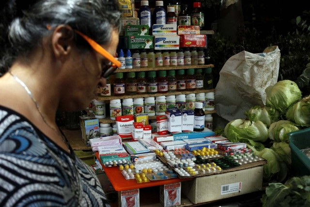 A woman walks past a fruit and vegetables stall selling medicines at a market in Rubio, Venezuela December 5, 2017. Picture taken December 5, 2017. REUTERS/Carlos Eduardo Ramirez