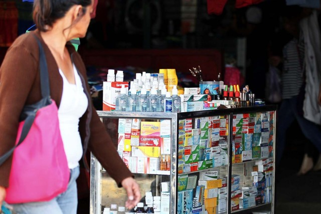 A woman walks past a stall selling medicines at Las Pulgas market in Maracaibo, Venezuela December 5, 2017. Picture taken December 5, 2017. REUTERS/Isaac Urrutia
